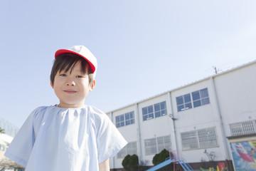 幼稚園の前に立つ男の子