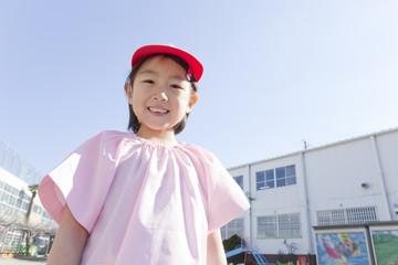 幼稚園の前に立つ女の子