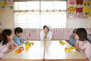 食事の挨拶をする幼稚園児と幼稚園教諭