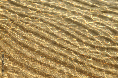 canvas print picture Shallow wavy illuminated waters background