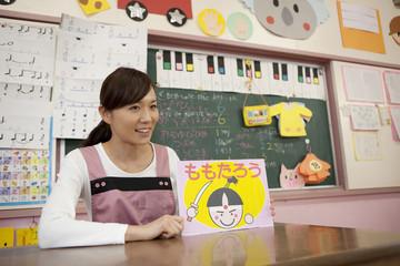 紙芝居を見せる幼稚園教諭