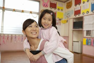 子供をおんぶする幼稚園教諭