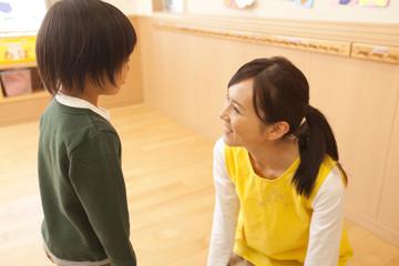 男の子と話をする保育士