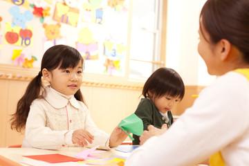 折り紙をする子供2人と保育士