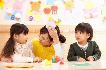 折り紙で遊ぶ子供2人と保育士