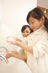 手を洗う女の子と保育士