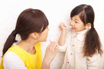 女の子に歯磨きの指導をする保育士