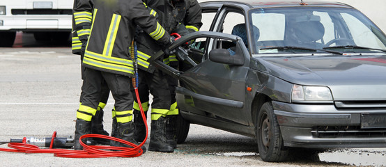 firefighters with shears open the car doors to free the injured