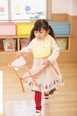椅子を持って歩く女の子