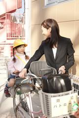 自転車に子供を乗せて歩く母親