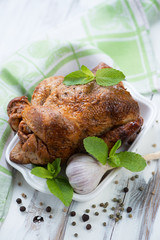 Smoked spicy chicken decorated with mint leaves, vertical shot