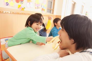 バナナを食べる子供3人と保育士