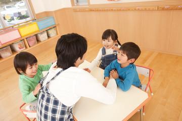 保育所で遊ぶ子供3人と保育士
