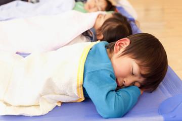 保育所で昼寝をする子供3人