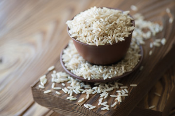Raw brown rice in ceramic tableware over wooden background