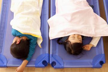 保育所で昼寝をする子供2人
