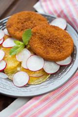 Roasted salmon cakes with sliced oranges and radish, studio shot