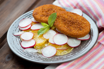 Roasted fish burgers with oranges and radish, horizontal shot