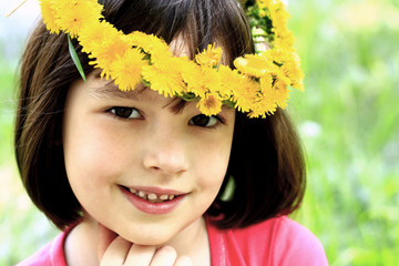 Little girl in a wreath of dandelions on nature background.