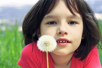 Little girl with white dandelion on nature background.