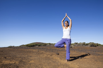 Young woman practicing tree yoga pose outdoor on a desert mounta