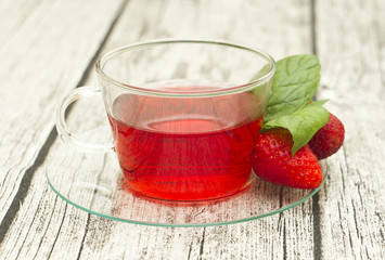 cup of tea with strawberries on wooden table