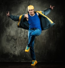 Man dancer in cap and jacket showing break-dancing moves