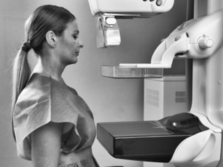 Woman taking a mammogram x-ray test. Mammography machine in a ho