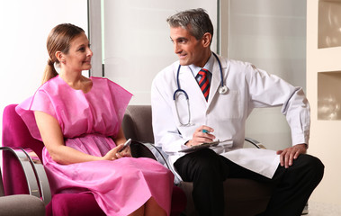 Happy male doctor speaking to woman patient about her health con