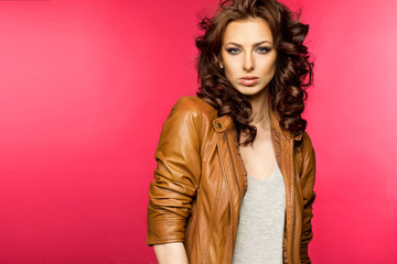 Beautiful young brunette in the leather jacket