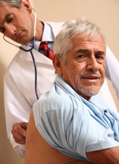 Male doctor examining elder patient at the hospital