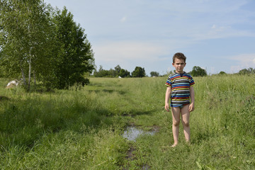 Rural boy stands barefoot on the road in the field.