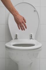 Hand greift ins geöffnete WC
