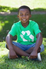 Young boy sitting on grass in recycling tshirt