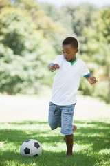 Little boy kicking a football in the park
