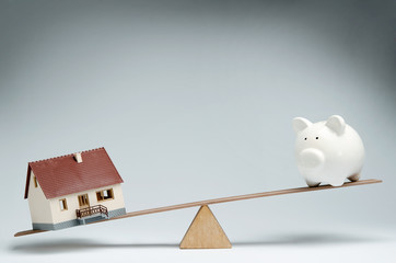 Model house and piggy bank balancing on a seesaw