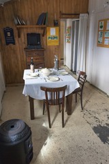The interior of the scientific research station at Camp Livingston on the South Shetlands Islands. A dining table and chairs with place settings.