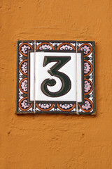 number three house address plate number on orange wall