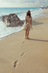 Beautiful young girl walking on the beach