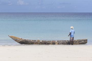Fischer mit langem Boot am Strand von Beau Vallon