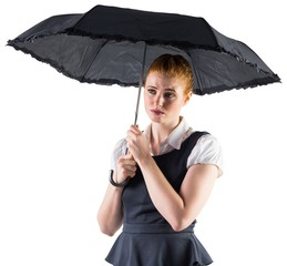 Pretty redhead businesswoman holding umbrella