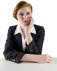 Thinking redhead businesswoman sitting at desk
