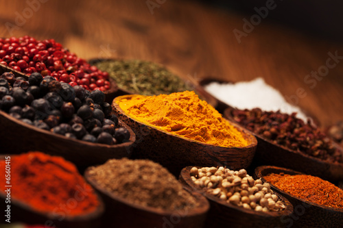 Spices and herbs in wooden bowls. - 65601415