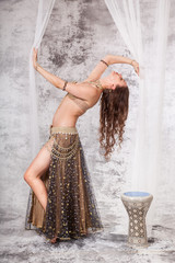 Retro belly dancer in backbend between drapes