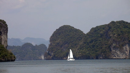 sailing yacht moves past the tropical islands