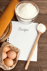 Recipe paper and baking cake ingredients, on a wooden table.