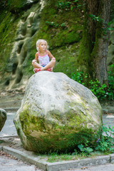 little girl sits on large stone
