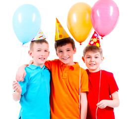 Three little boys with coloured balloons and party hat.