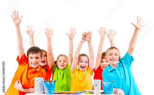 Group of children in colored t-shirts with raised hands.