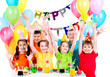 Group of children at the birthday party with raised hands.